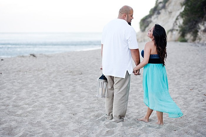 Romantic portrait of a couple trying engagement photo poses on the beach