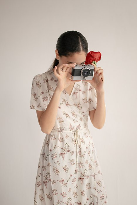 a girl in floral dress taking a photo with a film camera