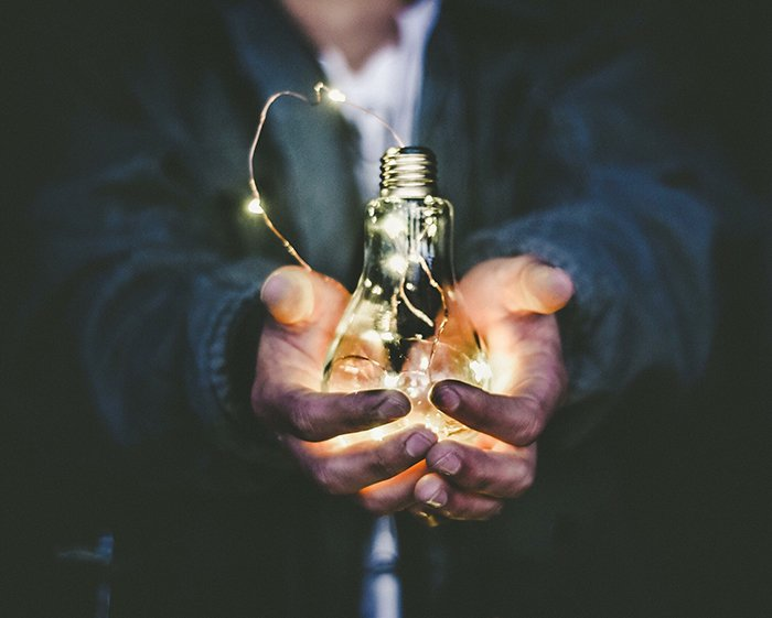 conceptual photo of a man holding a light bulb filled will fairy lights