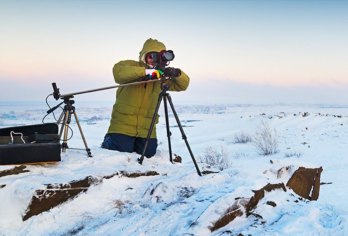 Man shooting a timelapse in the snow with a slider