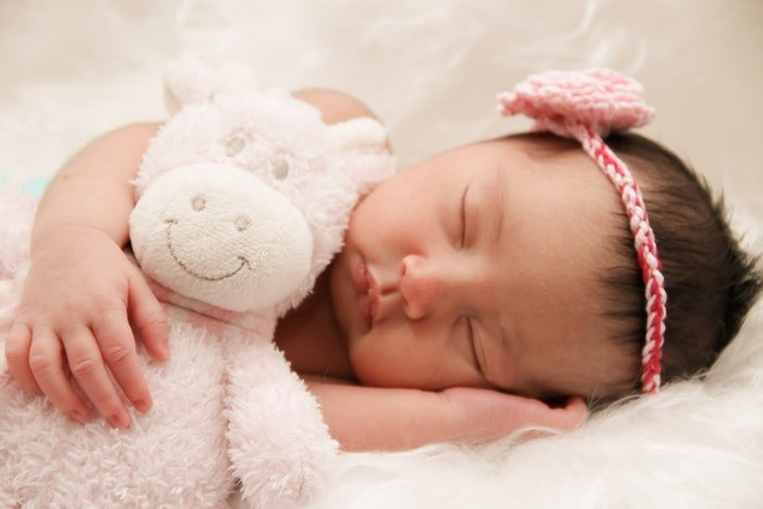 DIY newborn photography of baby sleeping with toy