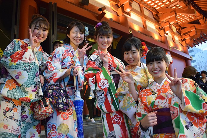 a group of Japanese girls in traditional dress posing for the camera
