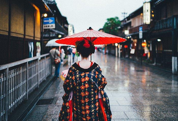 a Japanese Geisha walking down a street