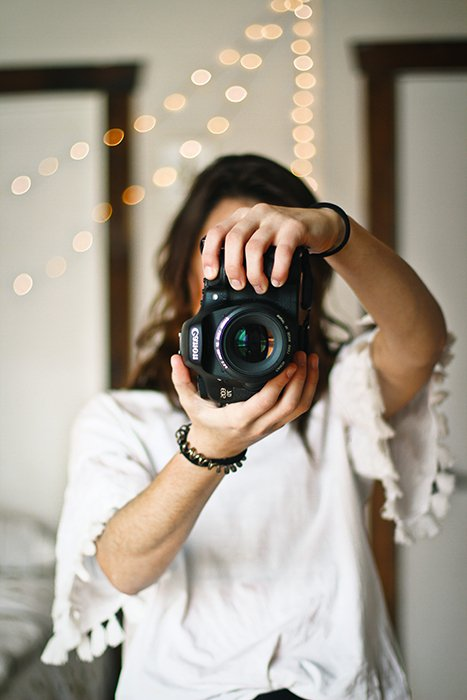 a female photographer holding a canon DSLR to the camera