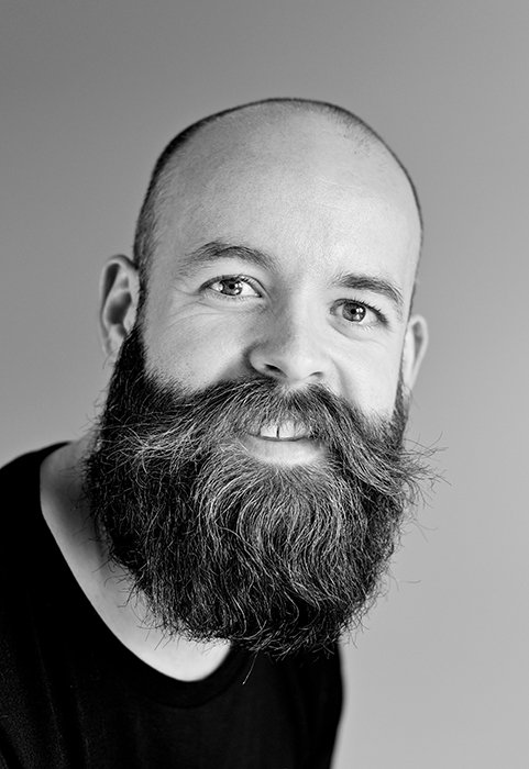 a professional black and white headshot photo of a bearded man