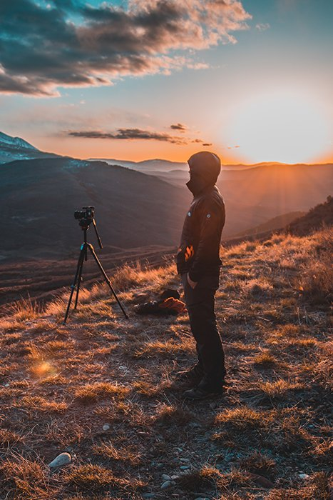 A man on a mountain with a tripod and camera