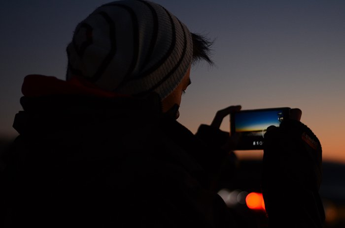 A man taking photos of a sunset