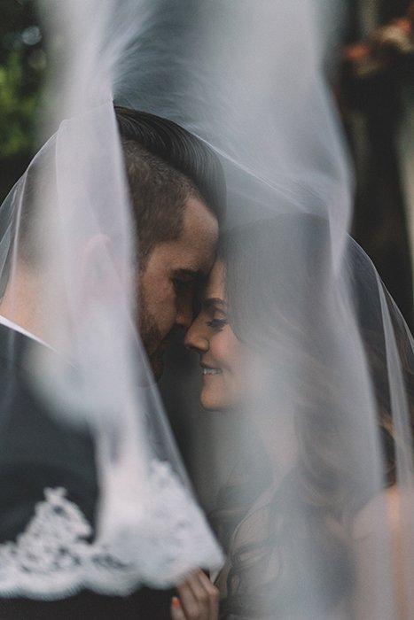 A bride and groom behind a wedding veil