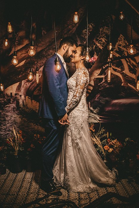 A bride and groom surrounded by ambient light bulbs