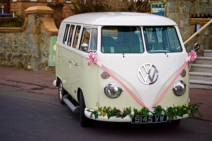 a VW camper van decorated with flowers and ribbons