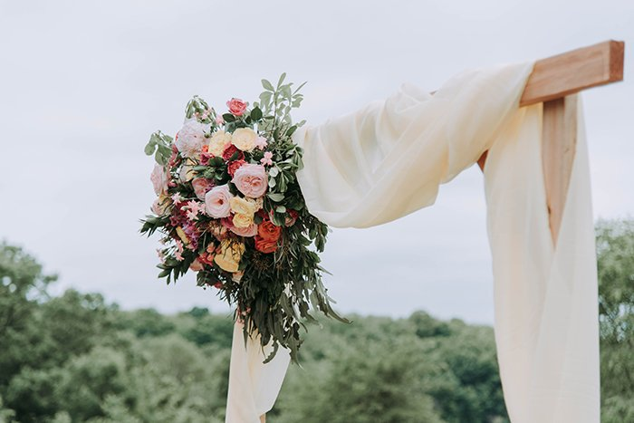 A wooden arch decorated with fabric and flowers