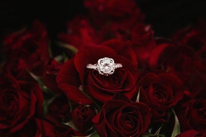A wedding ring among dark red roses