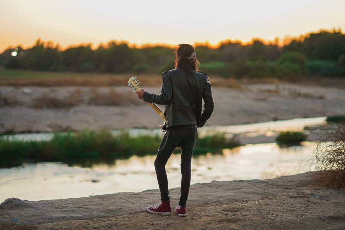 Photo of a guy with a guitar at sunset