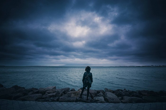 A person standing in front of a lake with dark skies