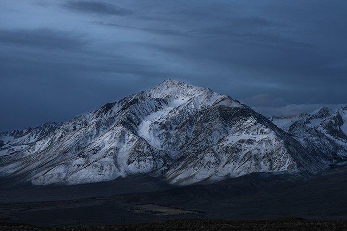 A snowy mountain peak with a dark sky