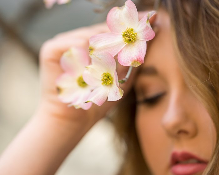 Photo of a girl holding pink flowers in front of her face