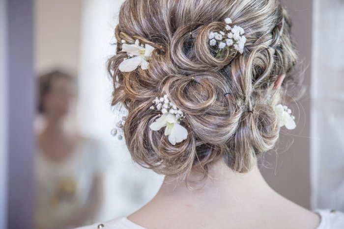A close up of a wedding hair style with small flowers