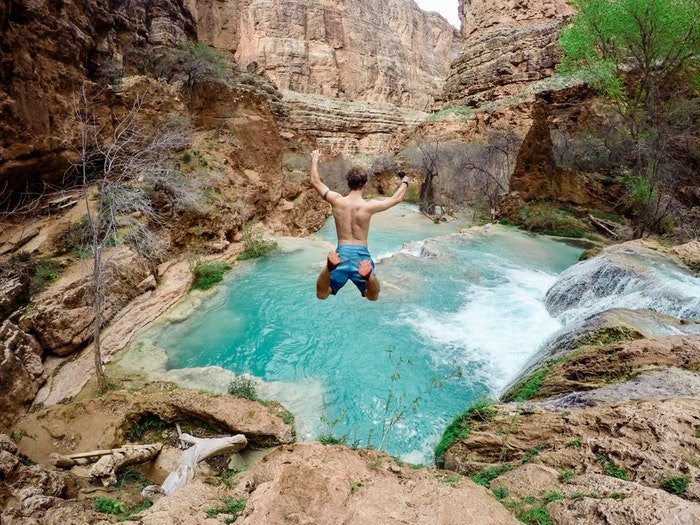 Man jumping into a pool of water surrounded by rocky mountains