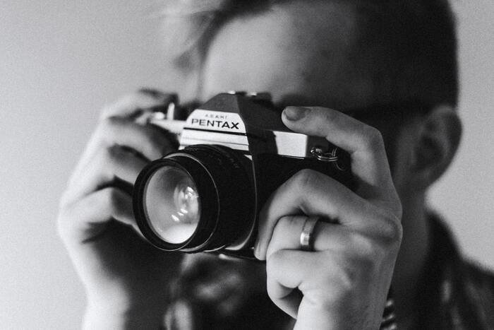 Black and white photo of a guy holding a camera