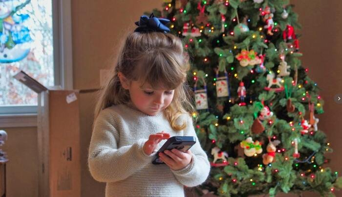 photo of a girl in front of a Christmas tree