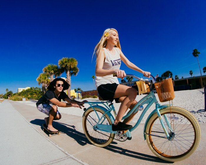 Photo of a girl riding a bike with a guy on a skateboard holding onto the bike