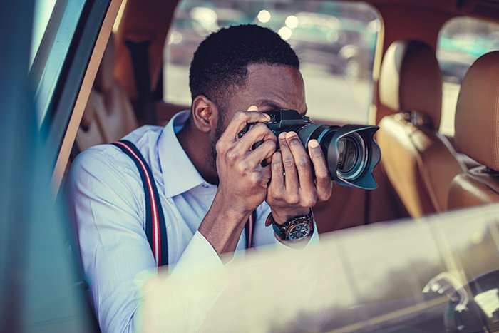 Photographer shooting from car with a DSLR.