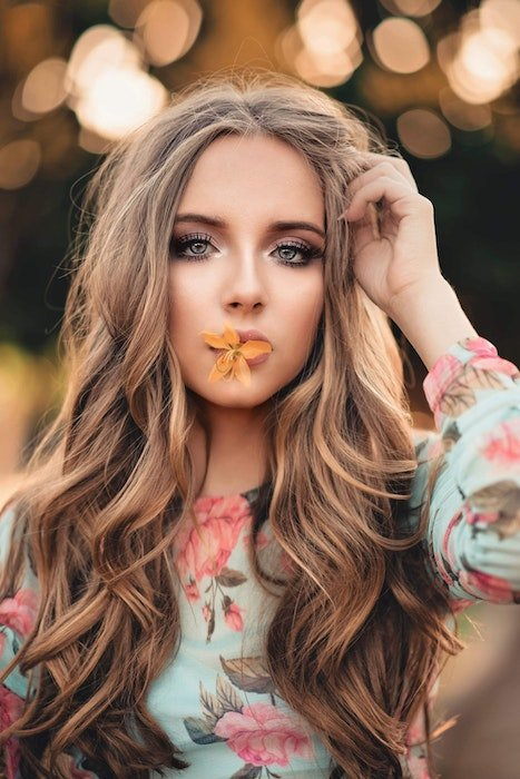 A beautiful woman with a flower in her mouth
