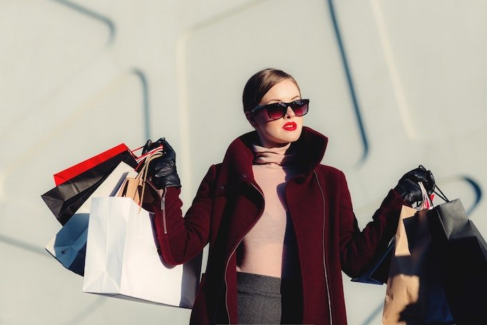 A fashion model holding shopping bags