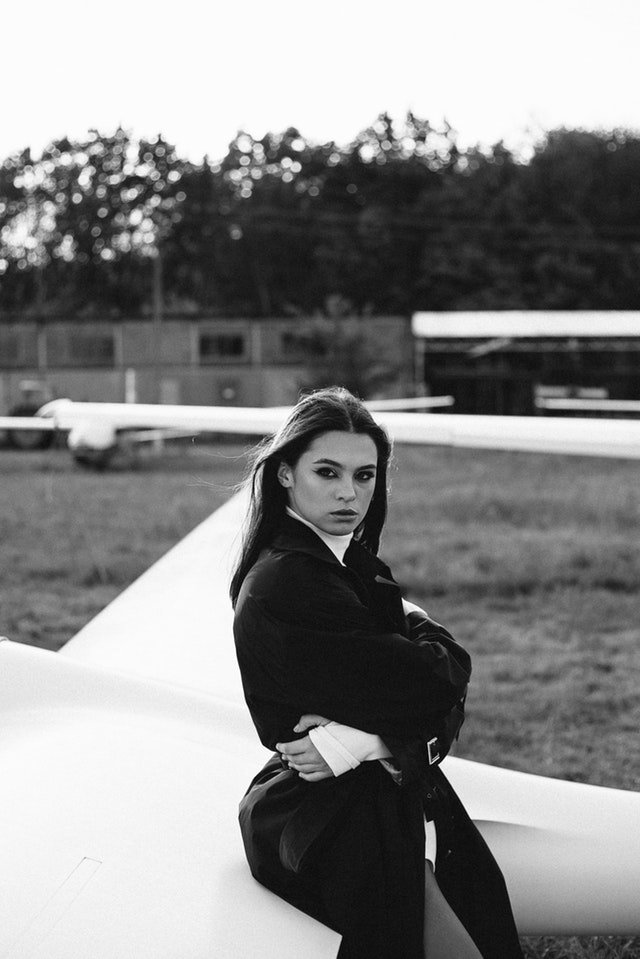 A black and white portrait of a female fashion model sitting on an airplane