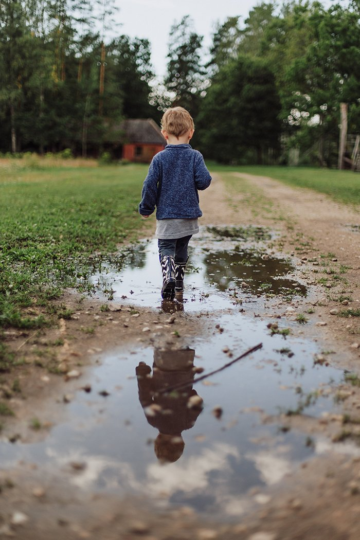 Photo of a little boy in boots walking on a dirt road