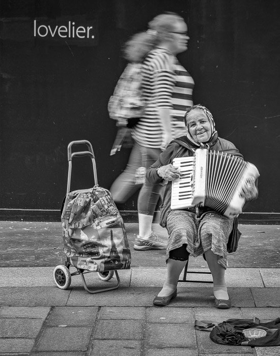 A woman playing accordion on the street with the text 'lovelier' above her head