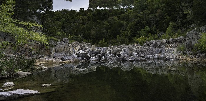 6-image panorama of a rocky lake under trees