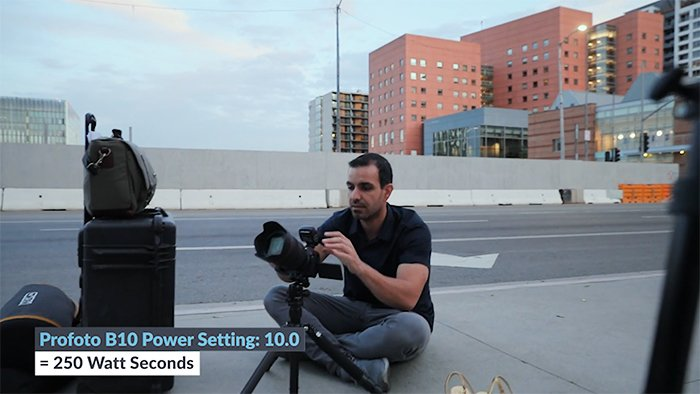 Photo of a guy sitting on a road setting up his camera