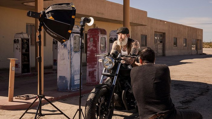 Photo of a guy on a motornike being photographed by a man