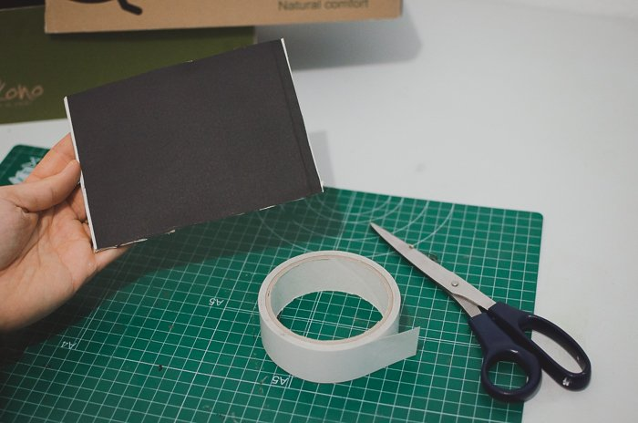 Cutting black paper and a shoe-box to make a DIY projector