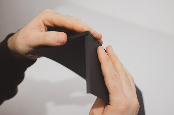 A person folding black paper to make a DIY phone lens projector
