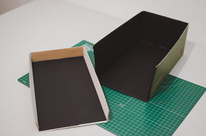 Gluing black paper to a shoe-box to make a DIY projector