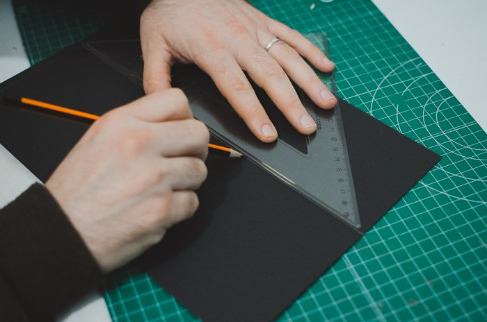 A person cutting cardboard to make a DIY phone projector