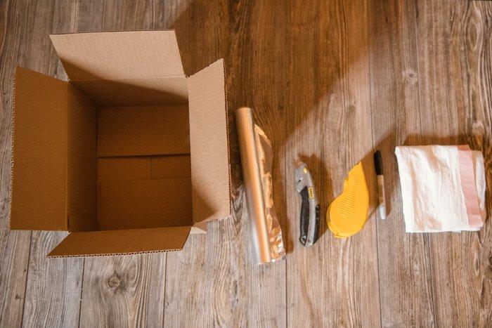 a cardboard box, aluminium foil, cutting knife, tape, stationary for making a DIY softbox