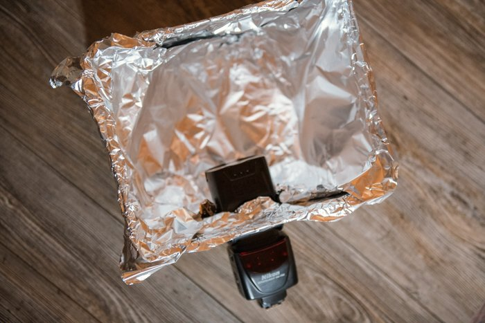 A camera flash inserted into a flap of a foil covered cardboard box