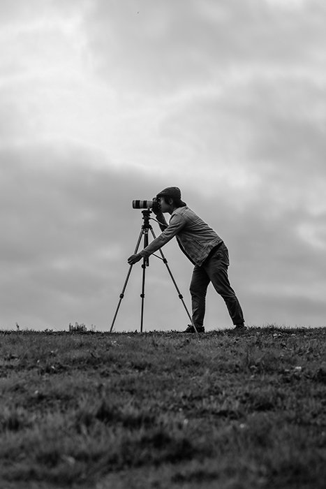 A man taking a shot through a DSLR on tripod in a gloomy landscape