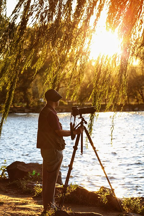 A photographer setting up a shot with a camera and tripod by a lake