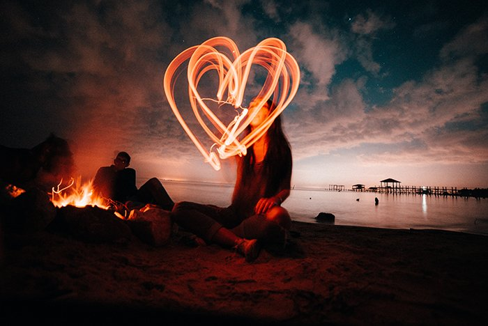 A girl making a heart shaped shaped with light painting