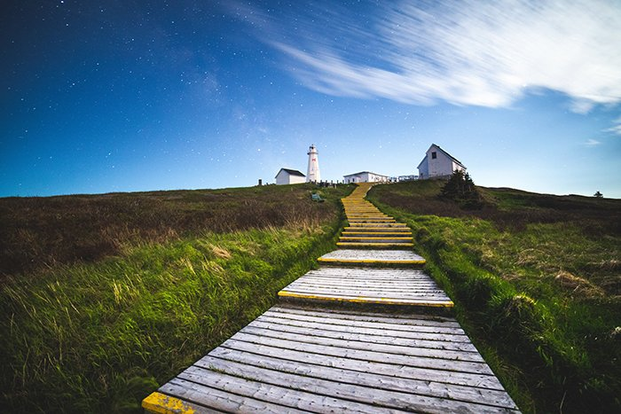 Wooden steps leading to a house on a grassy hill