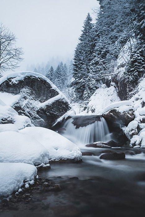 A waterfall among a snowy landscape