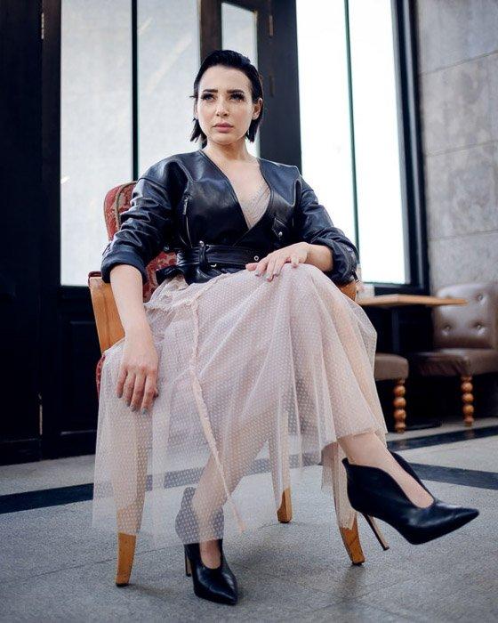 A glamorous fashion model sitting indoors