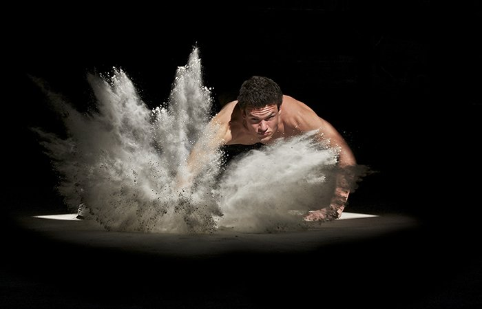 A man exercising surrounded by flour