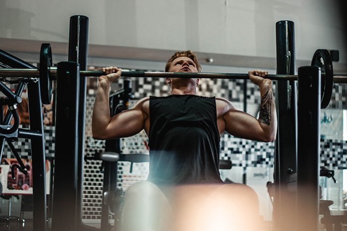 A man lifting weights in the gym for a fitness photoshoot