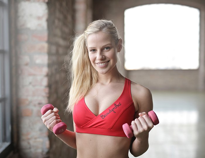 A woman lifting weights in the gym for a fitness photoshoot