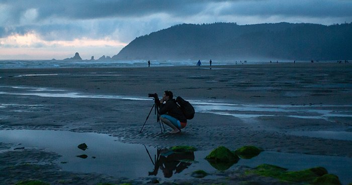 A photographer setting up tripod on a beach in low light